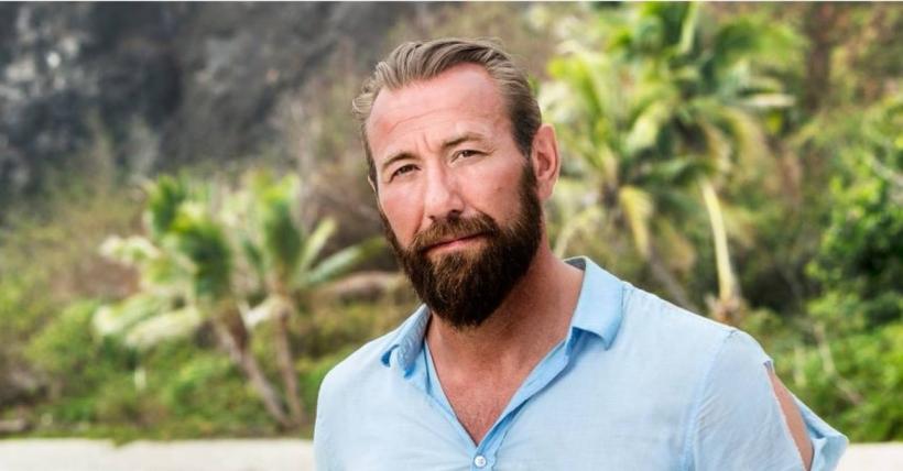 Robert Follin är stuntman och aktuell i Robinson. Han står på en strand i ljus skjorta.