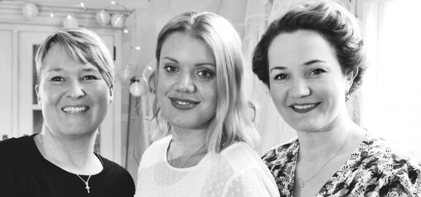 Tre kvinnor som ler, bilden är i svartvitt