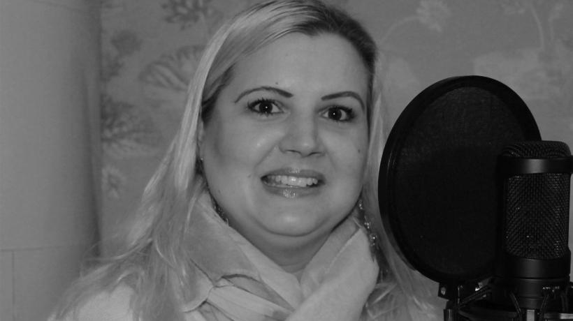 Malin Ovesson ler och tittar in i bilden. Bredvid sig har hon en mikrofon som hon pratar i under podcast-intervjun.