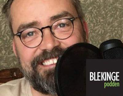 Leende man med skägg sitter framför en stor mikrofon
